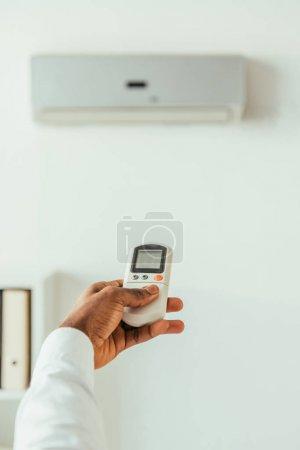Photo pour Vue recadrée de l'homme d'affaires afro-américain tenant télécommande tout en se tenant sous climatiseur dans le bureau - image libre de droit