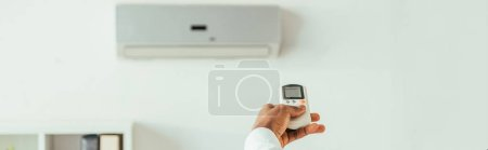 Photo pour Partial view of african american businessman holding remote controller while standing under air conditioner, panoramic shot - image libre de droit