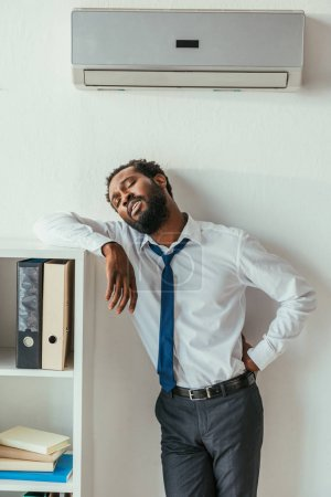 Photo for Exhausted african american businessman standing under conditioner and holding hand on hip - Royalty Free Image