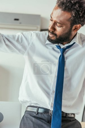 Photo for Exhausted african american businessman suffering from summer heat and looking at sweaty shirt - Royalty Free Image