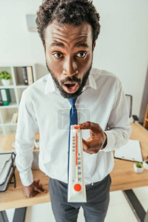 Photo for Shocked african american businessman looking at camera and showing thermometer - Royalty Free Image