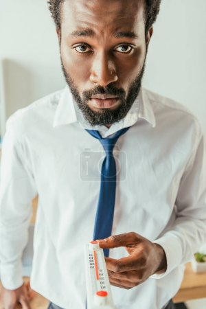 Photo for Exhausted african american businessman holding thermometer and looking at camera - Royalty Free Image
