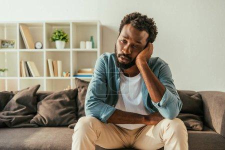 Photo pour Homme d'affaires américain africain réfléchi s'asseyant sur le divan à la maison et souffrant de la chaleur d'été - image libre de droit