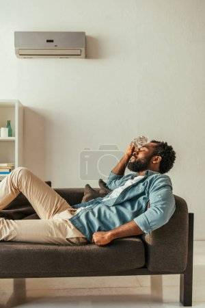 Photo pour Homme américain africain se trouvant sur le sofa avec les yeux fermés et retenant la bouteille avec l'eau près de la tête - image libre de droit