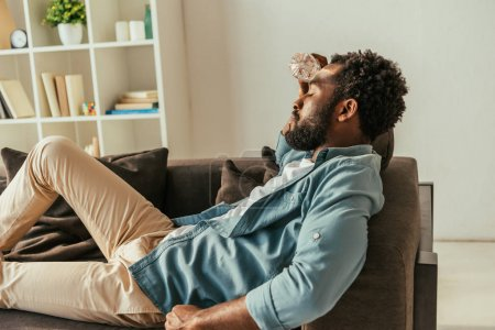 Photo for Exhausted african american man lying on couch with closed eyes and holding bottle with water near head while suffering from heat - Royalty Free Image