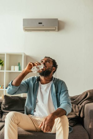 Photo for Thirsty african american man drinking water from plastic bottle while sitting on sofa at home - Royalty Free Image