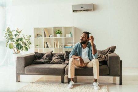 Photo pour Homme américain africain fatigué s'asseyant sur le sofa et retenant le contrôleur à distance de climatiseur tout en souffrant de la chaleur à la maison - image libre de droit