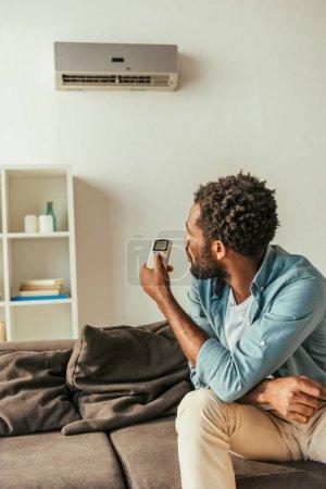 Photo pour Homme américain africain retenant le contrôleur à distance de climatiseur tout en s'asseyant sur le divan à la maison - image libre de droit