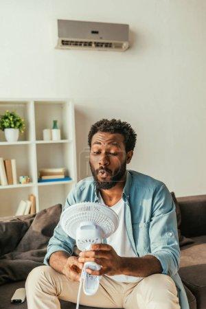 Photo pour Beau homme américain africain retenant soufflant ventilateur électrique tout en s'asseyant sur le sofa et souffrant de la chaleur à la maison - image libre de droit