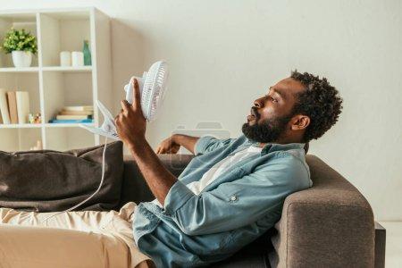 Photo pour Homme américain africain fatigué se trouvant sur le sofa avec le ventilateur électrique soufflant tout en souffrant de la chaleur d'été - image libre de droit