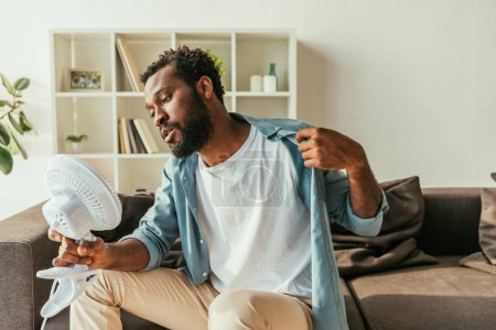Photo for Young african american man holding blowing electric fan while suffering from summer heat at home - Royalty Free Image