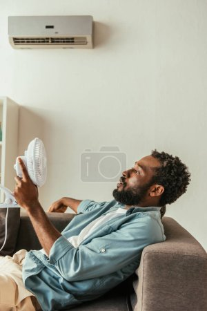 Photo for African american man holding blowing electric fan while lying on sofa under air conditioner - Royalty Free Image