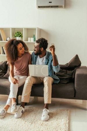 Photo pour Homme afro-américain joyeux utilisant un ordinateur portable et tenant la télécommande climatiseur tout en étant assis sur le canapé près souriant femme afro-américaine - image libre de droit