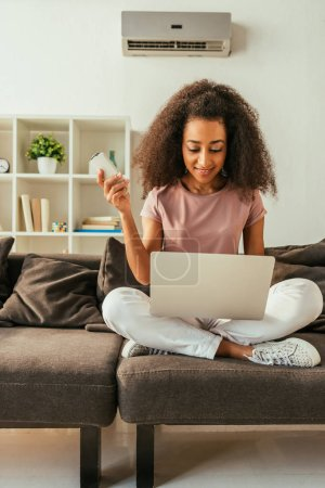 Photo for Smiling african american woman using laptop and holding air conditioner remote controller while sitting on sofa with crossed legs - Royalty Free Image