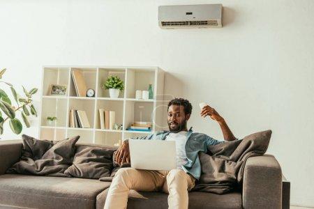 Photo pour Homme africain beau utilisant l'ordinateur portatif tout en s'asseyant sur le sofa sous le climatiseur et retenant le contrôleur à distance - image libre de droit