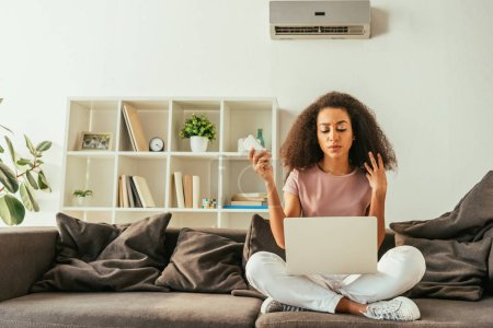 Photo for Serious african american woman using laptop and holding remote controller while sitting on sofa under air conditioner - Royalty Free Image