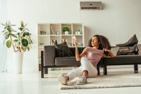 Photo for Attractive african american woman sitting on floor and using air conditioner remote controller while suffering from summer heat at home - Royalty Free Image