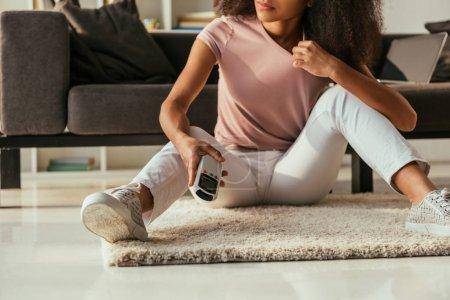 Photo pour Vue recadrée de femme américaine africaine s'asseyant sur l'étage et retenant le contrôleur à distance de climatiseur - image libre de droit
