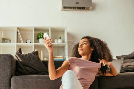 Photo pour Femme afro-américaine insatisfaite s'asseyant sur le sofa et utilisant le contrôleur à distance de climatiseur tout en souffrant de la chaleur d'été à la maison - image libre de droit