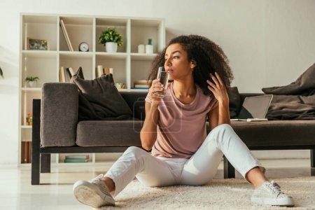 Foto de Mujer afroamericana reflexiva bebiendo agua mientras está sentada en el suelo y sufre de calor en casa - Imagen libre de derechos