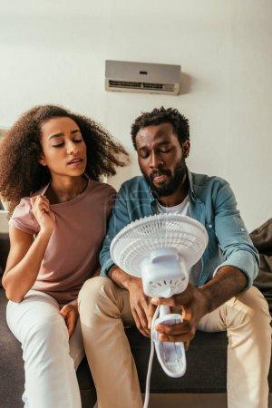 Photo pour Homme et femme afro-américains insatisfaits s'asseyant sur le sofa et retenant le ventilateur électrique soufflant - image libre de droit