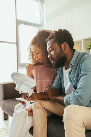 Photo pour Homme et femme américains africains souffrant de la chaleur d'été à la maison et retenant le ventilateur électrique de soufflage - image libre de droit