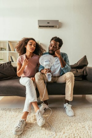 Photo for Young african american man and woman sitting on couch and holding electric fan while suffering from heat at home - Royalty Free Image