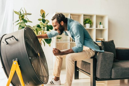 Photo pour Homme américain africain excité s'asseyant près du ventilateur électrique à la maison - image libre de droit