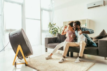 Photo for Excited african american man and woman sitting on sofa in front of blowing electric fan - Royalty Free Image