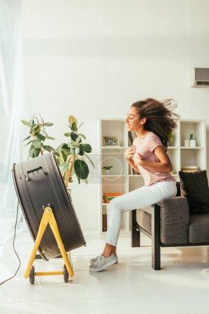 Photo pour Femme américaine africaine gaie s'asseyant devant le ventilateur électrique soufflant à la maison - image libre de droit