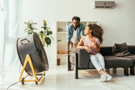 Photo for Exhausted african american man and woman suffering from summer in front of blowing electric fan - Royalty Free Image