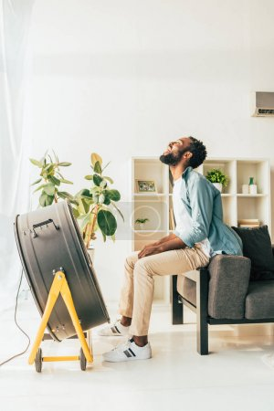 Photo pour Positive african american man sitting near blowing electric fan while suffering from summer heat at home - image libre de droit