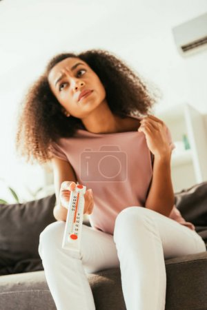 Photo for Exhausted african american woman suffering from summer heat while sitting on sofa and holding thermometer showing high temperature - Royalty Free Image