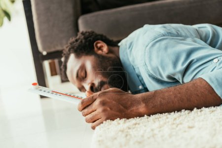 Photo for Exhausted african american man suffering from summer heat while lying on floor with thermometer in hand - Royalty Free Image