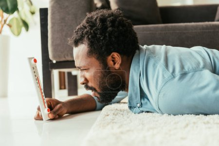 Photo for Shocked african american man looking at thermometer while lying on floor and suffering from summer heat - Royalty Free Image
