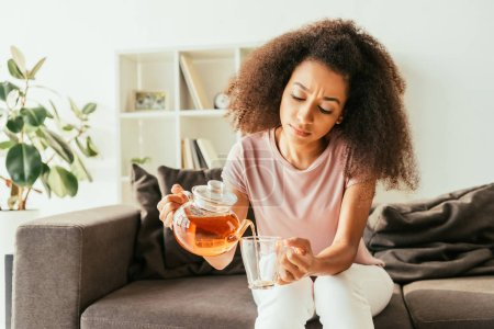 Photo for Young african american woman pouring tea into cup while sitting on sofa and suffering from heat at home - Royalty Free Image