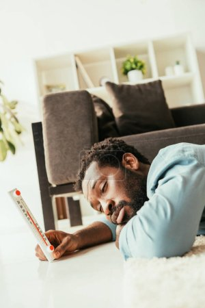 Photo for Exhausted african american man suffering from summer heat while lying on floor and holding thermometer - Royalty Free Image