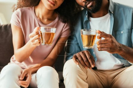 Photo for Cropped view of african american man and woman holding cups with tea while suffering from summer heat at home - Royalty Free Image