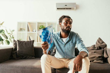 Photo for Unhappy african man waving with magazine while sitting on couch and suffering from heat - Royalty Free Image