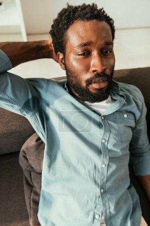 Photo pour Homme américain africain malheureux dans la chemise moite s'asseyant sur le divan et souffrant de la chaleur d'été - image libre de droit