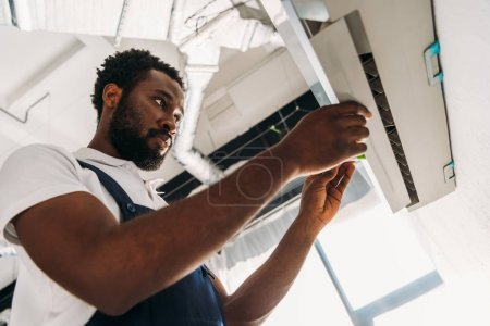 Photo for Concentrated african american repairman standing on ladder and fixing air conditioner - Royalty Free Image