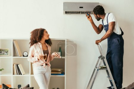 Photo pour Réparateur américain africain fixant le climatiseur près de la femme américaine assez africaine retenant le contrôleur à distance - image libre de droit