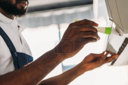 Photo for Cropped view of african american repairman cleaning air conditioner with brush - Royalty Free Image