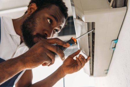 Photo for Serious african american repairman fixing air conditioner with screwdriver - Royalty Free Image
