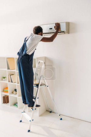 Photo for African american handyman in overalls standing on ladder and repairing air conditioner - Royalty Free Image