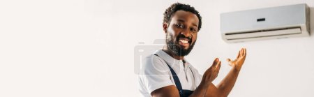 Photo for Panoramic shot of happy african american repairman smiling at camera and pointing with hands at air conditioner - Royalty Free Image