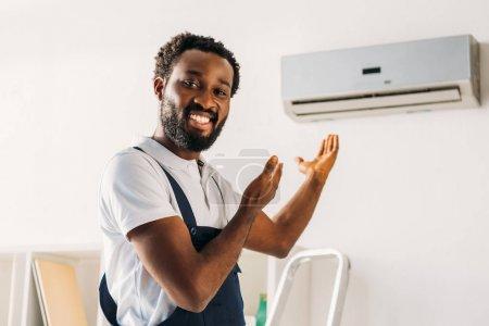 Photo pour Joyeux réparateur afro-américain souriant à la caméra et pointant du doigt le climatiseur - image libre de droit
