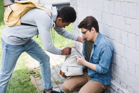 Foto de Niño afroamericano tomando mochila de niño asustado en gafas - Imagen libre de derechos