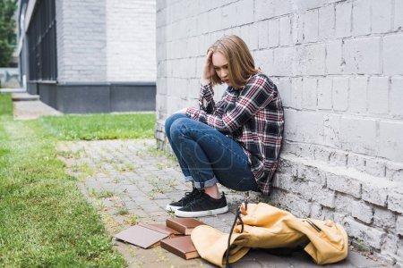 Foto de Sad and blonde teen in shirt and jeans sitting near wall among books - Imagen libre de derechos