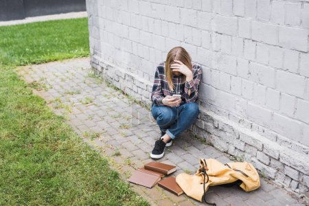 Photo for Disappointed and blonde teen in shirt and jeans sitting near wall and holding smartphone - Royalty Free Image